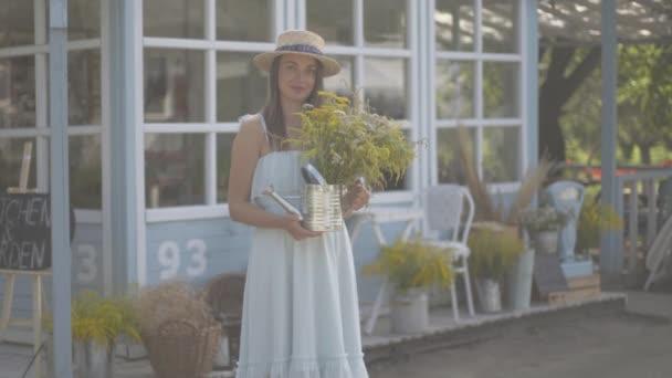 Roztomilá mladá žena v slaměném klobouku a bílých šatech, s úsměvem na kameře, zatímco před malým vesnickém domem čmuchá divoké květiny. Venkovský životní styl