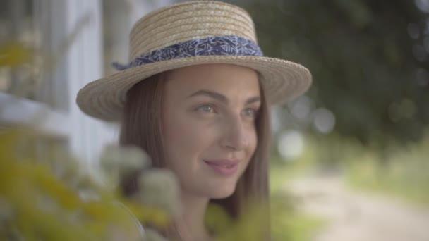 Blízkou tvář rozkošné mladé ženy v slaměném klobouku, která hledí ven a usmívá se venku. Emoce, životní styl venkova, koncepce přírodních krás.