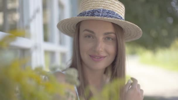 Close-up face of cute young woman in straw hat looking at the camera smiling happily outdoors. Emotion, rural lifestyle, natural beauty concept