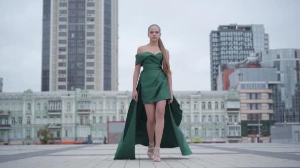 Krásná nádherná dívka v úžasném večerním zeleném oděvu fascinujícím na prázdném náměstí u mrakodrapu. Série skutečných lidí.