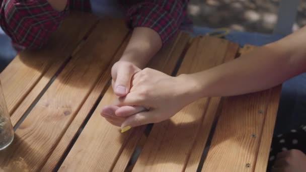 Közeli keze a fiatal boldog pár ül a szabadban az asztalnál kezében. Férfi és nő, miután dátumot. Szabadidő otthon
