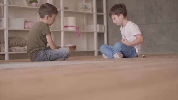 Two brothers sitting on the floor playing with the toy car sitting on the floor at home. Siblings spending time at home. Happy family, carefree childhood.