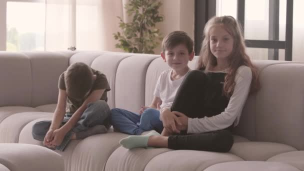 Portrét rozkošné starší sestry a dvou mladších roztomilého bratra sedícího na pohovce a dívali se na kameru s úsměvem. Vztah sourozenců. Bez bezstarostných dětství. Tři děti společně doma.