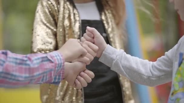 Těsné ruce tří dětí, které si navzájem drží palce, hrají dohromady. Děti si hrají na hřišti. Bez bezstarostných dětství. Tři šťastné děti venku