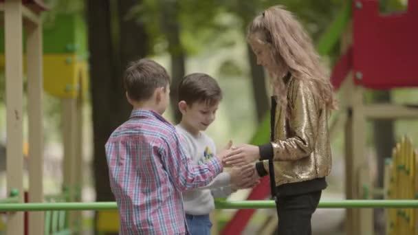 Drei niedliche Kinder spielen gemeinsam im Freien. Kinder auf dem Spielplatz. Sorglose Kindheit.