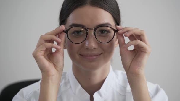Portrét docela mladý profesionální ženský doktor s brýlemi v dlaních kouká na kameru. Zaostření se pohybuje od obličeje k brýlím. Pojetí profese, lékařství a zdravotnictví.