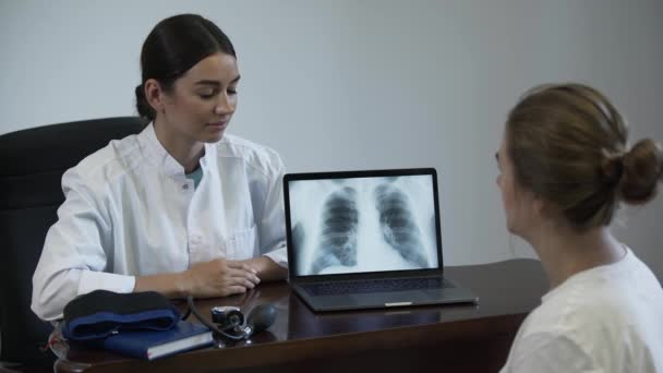 Professional female doctor tells something to female patient and showing on screen of laptop with lung x-ray image. Women shake hands and the doctor closes the laptop. Concept of profession, medicine
