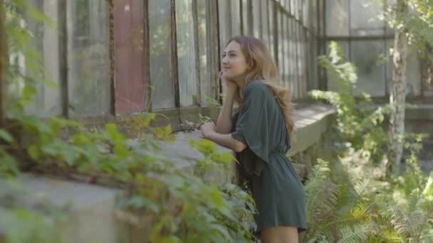 süße, glückliche junge Frau, die das große alte Gebäude betrachtet und die Vintage-Schönheit bewundert. Konzept von Sommerzeit, Weiblichkeit, Ruhetag