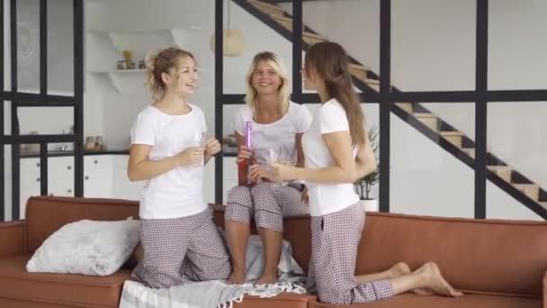 Három boldog barátnője ugyanabban a pizsamában időtöltést együtt otthon iszik alkoholt. A nők ünneplő, emelése kezekkel. Tyúk-party, pizsama Party. Lányok szórakozni beltéri
