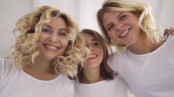 Portrét tří usmívající se atraktivních žen v bílých tričkách, které se dívaly do kamery a objímají je dohromady. Šťastné přítelkyně uvnitř. Bezstarostně životní styl