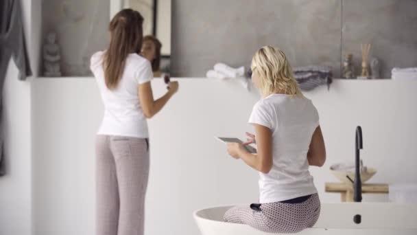 Két fiatal barátnői a pizsama időtöltést együtt a fürdőszobában tablettát. Női függők szerkentyű. Tyúk-party, pizsama Party. Lányok szórakozni beltéri.