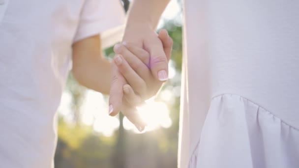 Nahaufnahmen von Frauen und kleinen Jungen, die im Park oder Wald stehen. glückliche Familie. ein Elternteil. Händchenhaltend. Mutterschaft, Elternschaft, Kindheit. Freizeit im Freien
