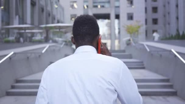 Pohled na Africkýho Američana v bílé košili, který chodí po schodech a mluví červeným mobilním telefonem. Obchodník nebo manažer v kanceláři.