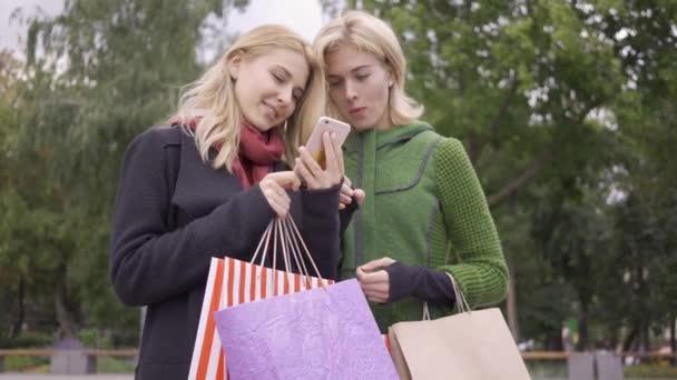 zwei schöne blonde Freundinnen, die mit Einkaufstüten auf der Straße stehen und auf ihr Handy schauen. zwei Modefrauen, die Rabatte im Internet prüfen. Unbeschwerter Lebensstil. Shopaholismus