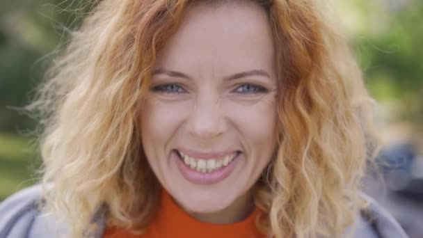 Close-up face of cute mature red-haired woman with curly hair smiling happily looking at the camera in the park. Emotions, happiness, good mood