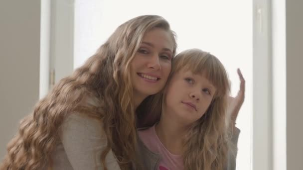 Happy blond caucasian mother hugging her irritated little daughter at home. Concept of motherhood, childhood, one parent. Difficulties in growing children