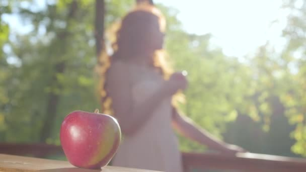 Close-up of a red apple with a redhead caucasian woman in the sunshine at the background. Snow White style. Fairy forest.