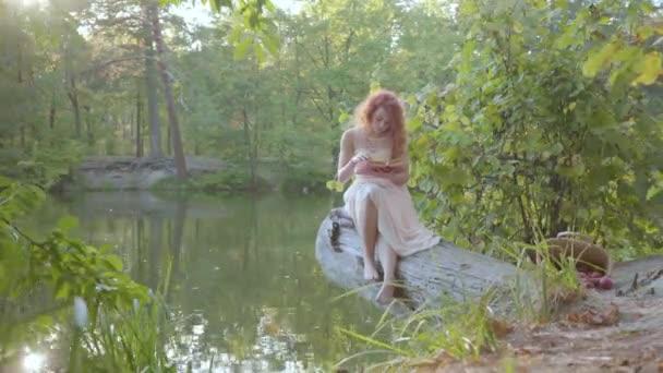 Krásná bělošská žena s červenými vlasy oblečenou v bílém, která sedí v slunečních paprscích na břehu řeky, pohlcovně čte knihu. Volný čas venku. Vzdělávací koncept. Souvislost s přírodou. Venkovský život.