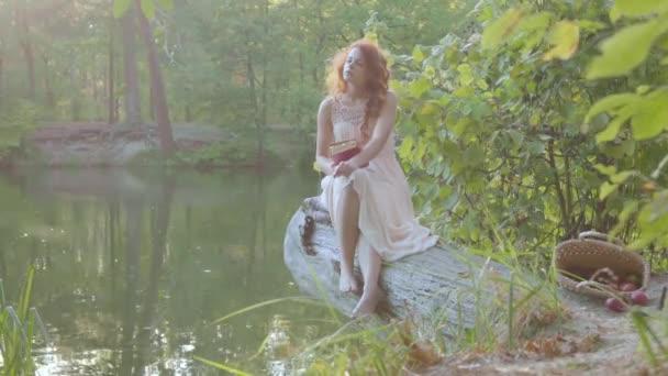 Okouzlující zrzavý běloch v bílém dlouhém oděvu, který sedí na břehu jezera a čte knihu v tmavě červeném obalu. Krásná dívka strávila venku teplé podzimní dny.