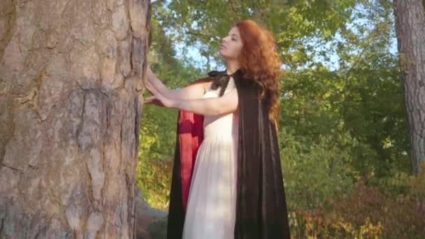 Krásná Kavkazská dívka s červenými vlasy v dlouhých bílých šatech a černou róbu s červeným obložením, který stojí vedle stromu v lese a dívá se jinam. Nymph užívající slunečný den.