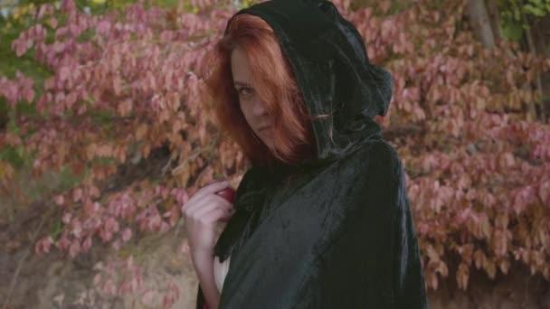 Tajemná zrzavá Kavkazská dívka v černém plášti, obracejí se k kameře a navrhla červené jablko. Pohádkovou nymfu nebo dryádu v podzimním lese. Styl sněžný bílý.
