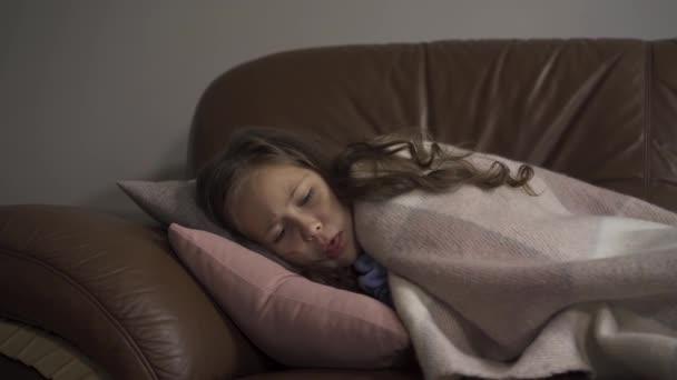Kranke junge kaukasische Mädchen husten, während unter Decke zu Hause liegen. Das Kind hat Fieber. Begriff Gesundheit, Krankheit, Krankheit, Erkältung, Behandlung