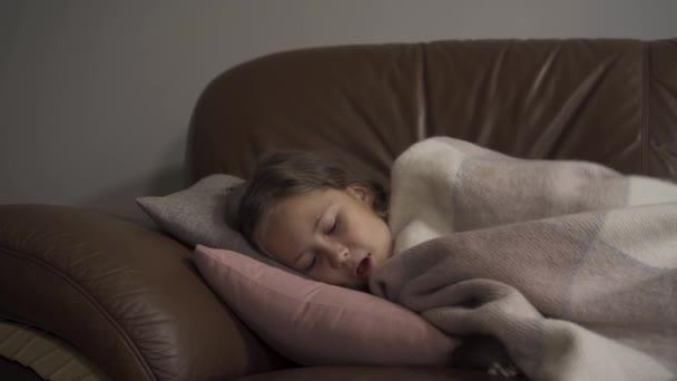 Kranke kaukasische Mädchen husten, während unter Decke zu Hause liegen. Das Kind hat Fieber. Begriff Gesundheit, Krankheit, Krankheit, Erkältung, Behandlung