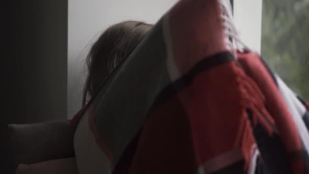 Kranke kaukasische Kind mit einer warmen Decke bedeckt sitzen auf Fensterbank zu Hause. Kleine brünette Mädchen mit Fieber Blick auf das Fenster traurig. Begriff Gesundheit, Krankheit, Krankheit, Kälte, Behandlung.