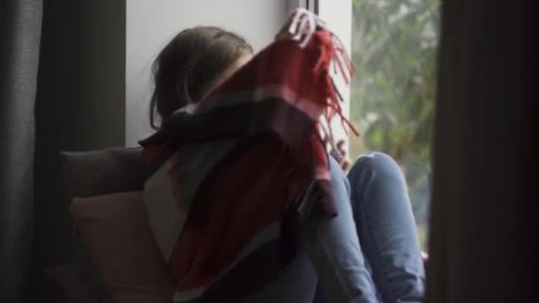 Kranke Brünette Mädchen mit einer warmen Decke auf Fensterbank zu Hause sitzen bedeckt. Kaukasisches Kind mit Fieber, das traurig auf das Fenster schaut. Begriff Gesundheit, Krankheit, Krankheit, Kälte, Behandlung.