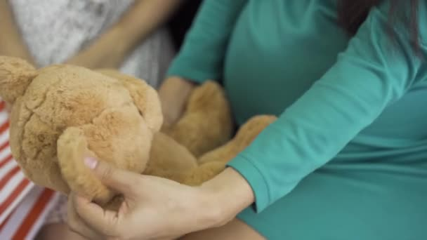 Close-up of soft yellow teddy bear. Female hands holding the gift. Pregnant woman in silk blue-green dress with a present for her unborn child.