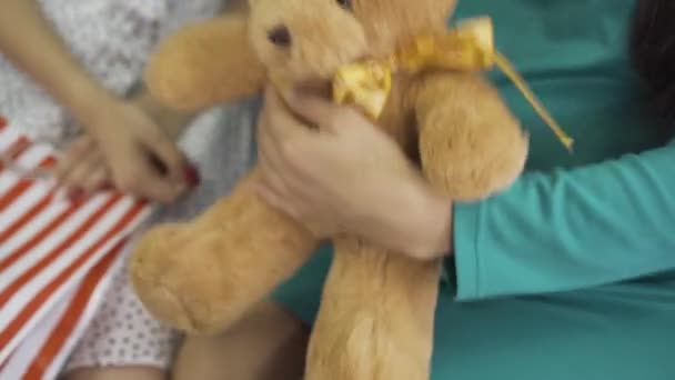 Close-up of soft yellow teddy bear with a silk bow. Female hands holding the gift. Pregnant woman in silk blue-green dress with a present for her unborn child.