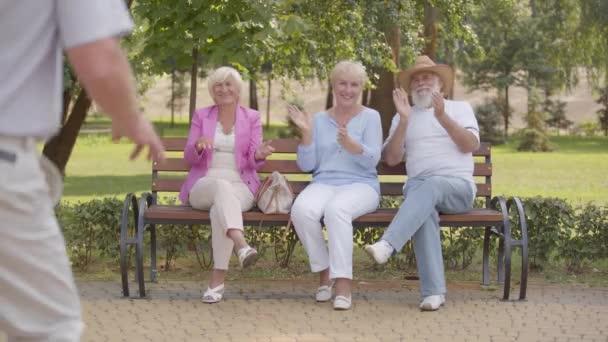 Tři běloši seděli na lavičce a tleskali svému veselému příteli, který tancoval. Starší společnost se baví ve slunečném odpoledni v parku. vdané dospělé páry odpočívající venku.