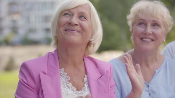 Dvě pozitivní starší ženy tleskají rukama a na něco se dívají. Hezké ženy středního věku sledují nějaké představení. Starší dáma odmítá účast v nějaké zábavě.