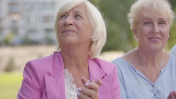 Detailní záběr dvou pozitivních starších žen, které tleskají rukama a na něco se dívají. Hezké ženy středního věku sledují nějaké představení. Starší dáma odmítá účast v nějaké zábavě.