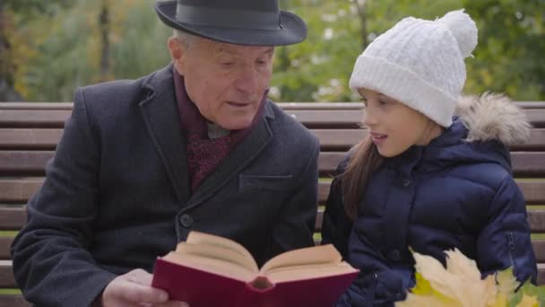 Close-up portrait of a mature Caucasian man in classic clothes sitting on the bench with his granddaughter and reading a book in red cover. Pretty smiling girl listening to her wise grandfather.
