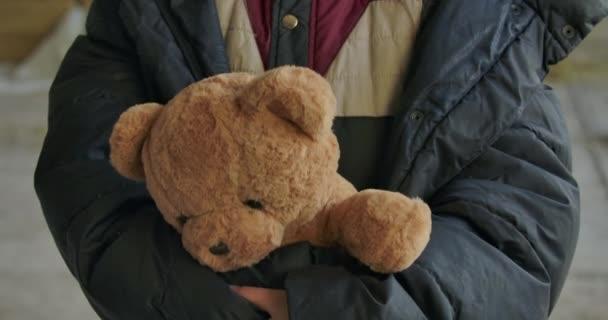 Egy közeli kép hajléktalan lányok kezéről, amint Teddy macit fognak. Fáradt menekült áll a gyönyörű játékával..