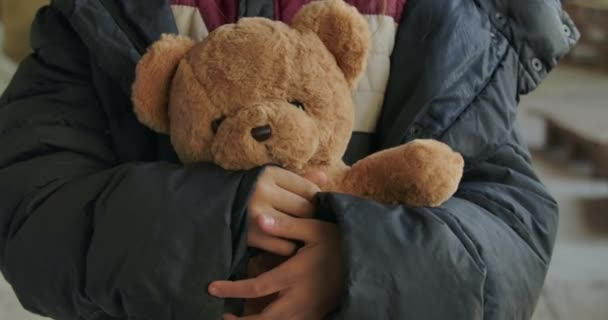 Piszkos lányok kezei Teddy macival a kezükben. Fáradt szíriai menekült áll a gyönyörű játékával..