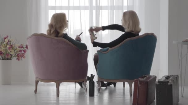Back view of rich Caucasian women sitting in comfortable armchairs and scaterring money. Senior ladies spending vacations with a bottle of wine and cigars. Slow motion.