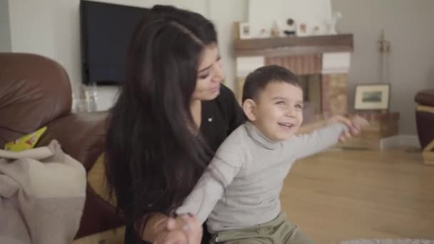 Portrait of a happy Middle Eatern mother and son imitating airplane flight. Cheerful woman with long dark hair playing with a smiling little boy at home. Camera moving dynamically following people.