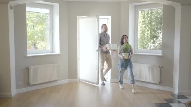 Young Caucasian couple entering their new house holding box and home plant. Happy family hugging as moving in a big light house. Start of new life.