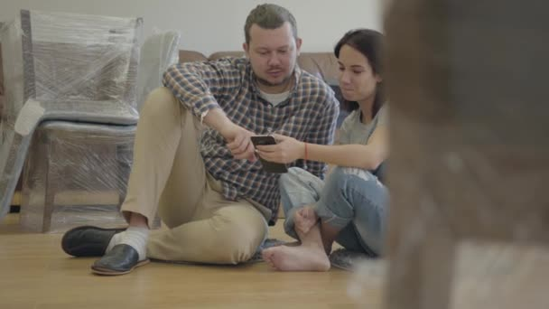 Close-up of a happy Caucasian family sitting on the floor in living room with new furniture and using smart phone. Smiling couple moving in their new house. Start of new life.