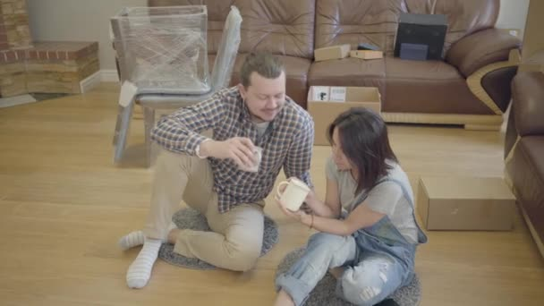 Young Caucasian couple drinking tea or coffe on the floor in living room with new furniture. Happy family moving in their new house. Beginning of new life.