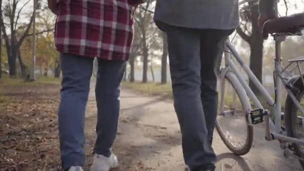 Nahaufnahme zweier Paar Erwachsenenbeine in Turnschuhen, die mit dem Fahrrad entlang der Gasse im Park laufen. Kamera geht hoch. reife Rentnerfamilie, die abends im Freien bummelt. Gemeinsam altern, ewige Liebe