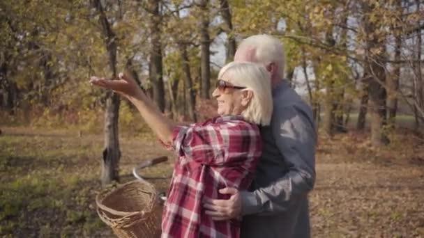 Šťastný bělošský pár v důchodu, který stojí na slunci v podzimním lese nebo parku a usmívá se. Boční pohled na dospělé rodiny trávit čas spolu venku. Stárnoucí, věčný koncept lásky.