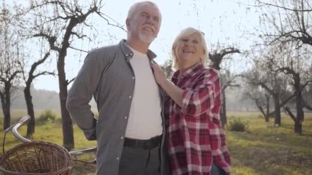Portrét šťastného staršího bělošského páru, který stojí na slunci v mlhavém parku a mluví. Usmívající se dospělá rodina tráví podzimní večer venku. Stárnoucí, věčný koncept lásky.
