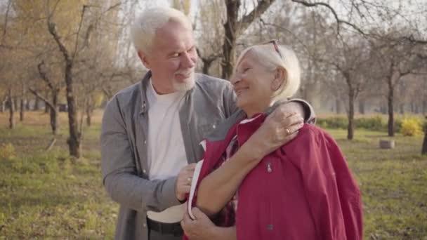 Detailní portrét šťastného bělošského páru v důchodu, stojícího na slunci v podzimním lese a objímajícího se. Starší evropská rodina tráví slunečný večer venku. Stárnoucí, věčný koncept lásky
