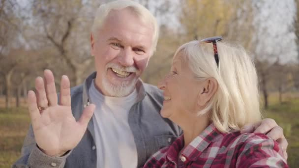 Nahaufnahme eines lächelnden kaukasischen Rentnerehepaares, das in die Kamera winkt. reife europäische Familie, die im Sonnenlicht im herbstlichen Wald steht. Gemeinsam altern, ewige Liebe