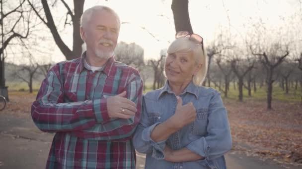 Starší bělošský manžel a žena stojí na slunci v podzimním parku a mluví před kamerou. Starší evropský pár gestikulující a usmívající se venku. Stárnoucí, věčný koncept lásky.