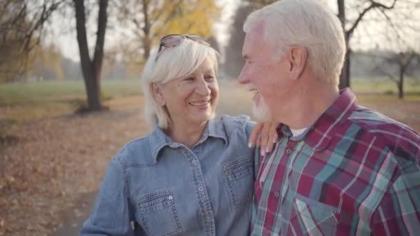 Šťastná bělošská dospělá rodina se na sebe dívá a usmívá se. Starší evropský pár stojící na slunci v podzimním parku. Manžel a manželka tráví večer venku. Stárnout spolu, věčná láska.