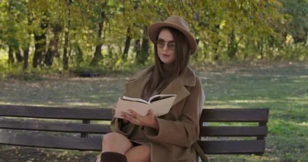 Chytrá elegantní běloška v brýlích a hnědém klobouku sedící na lavičce a obracející stránky knihy. Krásná evropská dívka čte poezii v podzimním parku. Kino 4k záběry Prores Hq.